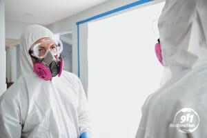 disaster restoration technicians wearing hazmat suits