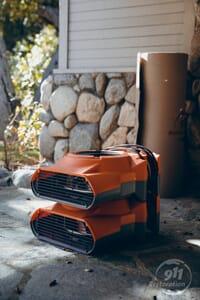 disaster restoration equipment on stoop of house